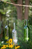 Glasflaschen mit Teelichtern an rustikalem Seil aufgehängt