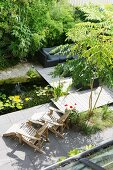 Garden pond, wooden lounger and sofa on wooden deck next to bamboo