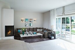 Elegante Loungeecke neben Gaskamin mit Kaminfeuer und Terrassenfenster