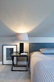 Bedside lamp on black bedside table in elegant bedroom