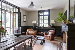 Comfortable leather armchairs and rustic tables in traditional-style living area with open balcony door