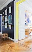 Verschiedene, gerahmte Bilder an schwarzer Wand in restauriertem Flur mit Fischgrätparkett