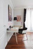 Schreibtisch mit schwarz-weißem Armlehnstuhl vor Fenster