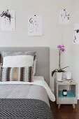 Sketches of women hung on wall above bed and bedside cabinet