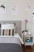 Aufgehängte Skizzen mit Frauenmotiven über Bett und Nachtkästchen
