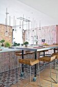 Designer bar stools at long dining table on castors in front of island counter