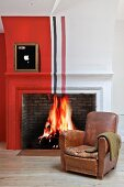Vintage leather armchair in front of fire in traditional fireplace painted with red, white and black stripes