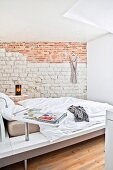 Designer bed and exposed stone and brick wall in bright bedroom