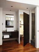 Exotic-wood parquet floor, countertop sink and open door leading to separate toilet in elegant bathroom