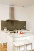 Breakfast bar and bar stools in white designer kitchen