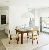 Simple dining set under white lampshade against partition wall with fitted kitchen in background