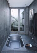 Sunken bathtub in grey modern bathroom