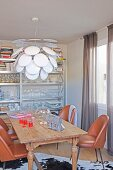 Rustic wooden table, leather chairs and white pendant lamp in front of crockery and books on metal shelves