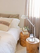 Stacked books and table lamp on tree-stump stools used as bedside tables next to double bed