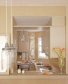 View through serving hatch into beige kitchen