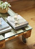 Books and tealights on pallet table with castors and glass top