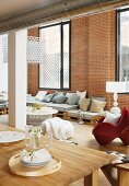 Dining area and lounge area in loft apartment with brick wall