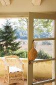 Raffia fan hung on open balcony door with view of landscape