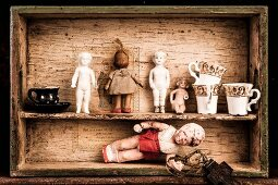 Antique dolls and crockery on wooden crate