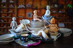 Antique dolls and crockery in front of display case