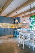 Cement tiles, kitchen counter and round dining table in open-plan country-house kitchen