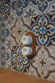 Vintage-style electrical sockets mounted on ornamental, floral wall tiles