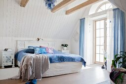 Exposed wooden beams in vintage-style country-house bedroom