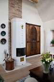 Rustic cupboard with lattice doors next to white tiled stove in country-house interior