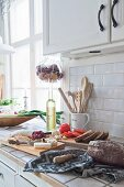 Rustic cheese and charcuterie board in white country-house kitchen