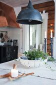 Black ceiling lamp above dining table in rustic kitchen-dining room
