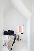 Weisses Schlafzimmer mit Doppelbett und schwarzer Bettwäsche