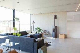 Offenes Regal mit Glasboden, graue Polstercouch und Kamin in offenem Wohnraum mit Glasfront und Betonwand