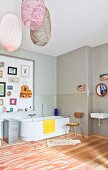 Bathtub, wall decorated with various items and designer pendant lamps in spacious bathroom of period apartment