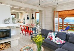 Sofa, dining table and open-plan kitchen in spacious interior of wooden house