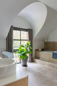 Stone tiles, bathtub and houseplant in front of window in elegant bathroom
