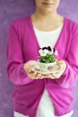 Viola planted in coffee cup held by child
