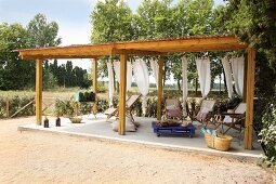 Wooden loungers on concrete floor below wooden pergola