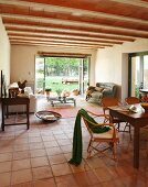 Dining area and couch on terracotta-tiled floor in Mediterranean interior