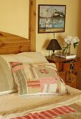 Patchwork scatter cushions on bed next to bedside table and painting