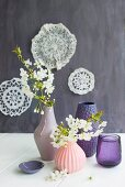Flowering branches in vases with structured surfaces in various shades of pink and purple