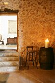 Lit pillar candle on top of old wooden barrel against stone wall