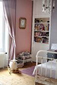 Rocking sheep and dolls' bed in vintage-style girl's bedroom