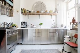 Stainless steel fronts and open-fronted shelves in kitchen