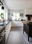 White L-shaped kitchen counter, black pendant lamps and island counter made from old workbench