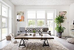 Rustic coffee table made from reclaimed wood and grey couch in front of French windows in living room
