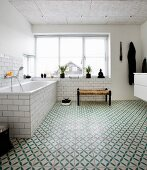 Bathtub below large window in bathroom with green and white patterned floor tiles