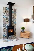 Wood-burning stove on strip of patterned tiles on wall and floor