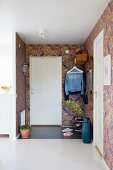 Front door and brightly patterned wallpaper in foyer