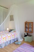 Mosquito net over bed in child's bedroom in pastel shades