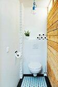 Toilette mit rustikaler, recycelter Bretterwand und Ornamentfliesenboden